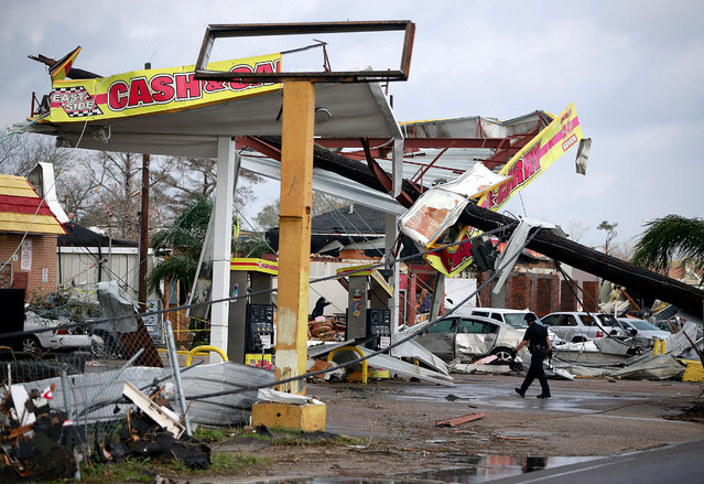 A police officer walks through a damaged gas station along Chef Menture Avenue after a tornado touched down in the eastern part of the city on February 7, 2017 in New Orleans, Louisiana. (Photo by Sean Gardner/Getty Images)