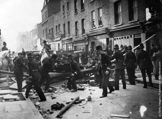 British policemen dismantle a barrier near Mark Lane, London, 1936