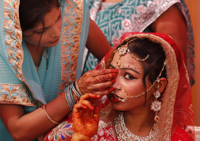 An Indian underprivileged bride gets her jewellery adjusted by a relative during a mass marriage ceremony in New Delhi, India, March 10, 2016. Fourteen  underprivileged couples tied up the nuptial knot in the mass marriage ceremony organised by various social organisations. (Photo by Rajat Gupta/EPA)