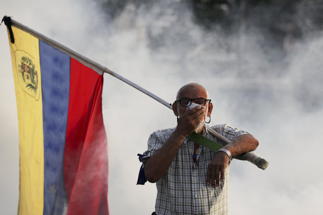An opponent to Venezuelan President Nicolas Maduro carrying a Venezuelan flag covers his face amid tear gas fired by soldiers loyal to Maduro during an attempted military uprising to oust Maduro in Caracas, Venezuela, Tuesday, April 30, 2019. (Photo by Boris Vergara/AP Photo)