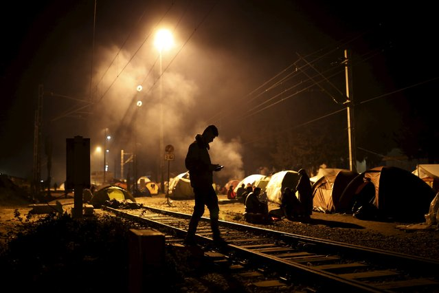 A migrant walks along railway tracks at a makeshift camp at the Greek-Macedonian border near the village of Idomeni, Greece, March 28, 2016. (Photo by Marko Djurica/Reuters)