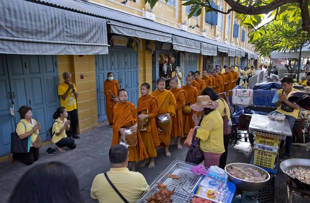 Thai people make offerings to Buddhist monks who collect alms close to The Grand Palace in which King Maha Vajiralongkorn's coronation takes place on Sunday, May 5, 2019, in Bangkok, Thailand. King Maha Vajiralongkorn was officially crowned amid the splendor of the country's Grand Palace, taking the central role in an elaborate centuries-old royal ceremony that was last held almost seven decades ago. (Photo by Gemunu Amarasinghe/AP Photo)