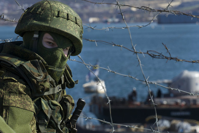 Russian soldiers guard a pier where two Ukrainian naval ships are moored, in Sevastopol, Ukraine, on Wednesday, March 5, 2014. Ukraine's new prime minister said Wednesday that embattled Crimea must remain part of Ukraine, but may be granted more local powers. Since last weekend, Russian troops have taken control of much of the peninsula in the Black Sea, where Russian speakers are in the majority. (Photo by Andrew Lubimov/AP Photo)