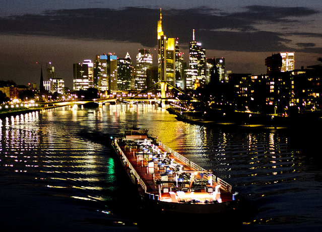 A cargo barge is seen on the river Main with bank buildings in background in Frankfurt, Germany on April 15, 2019. (Photo by Michael Probst/AP Photo)