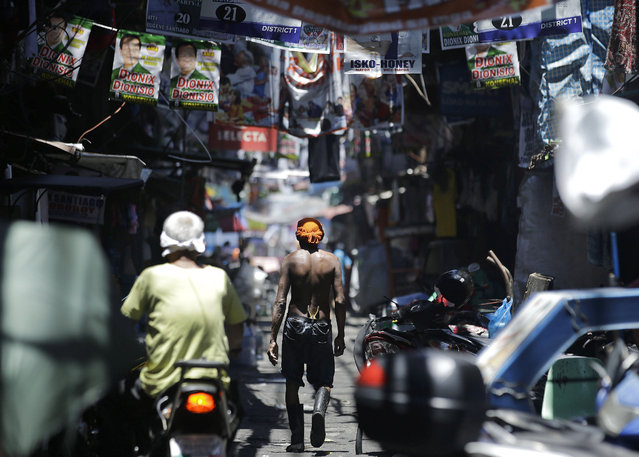 In this Thursday, May 9, 2019, photo, a man walks past election banners in the slum district of Tondo, Manila, Philippines. Philippine President Rodrigo Duterte's name is not on the ballot but Monday's mid-term elections are seen as a referendum on his phenomenal rise to power, marked by his gory anti-drug crackdown and his embrace of China. (Photo by Aaron Favila/AP Photo)