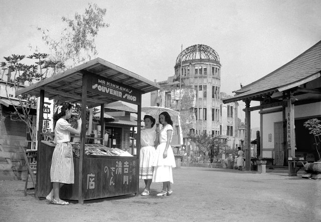 On August 3, 1951, six years after an atomic bomb was detonated above this spot in Hiroshima, a souvenir shop stands in the street near the shattered dome of the Industry Hall. The shop is operated by Kiyoshi Yoshikawa, who was injured in the blast. (Photo by AP Photo/Kyodo via The Atlantic)