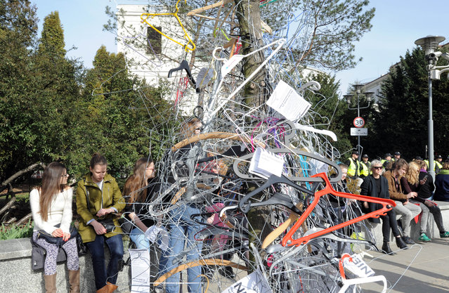 """People sit next to a tree covered with hangers, symbolizing an illegal abortion,  in front of the Polish parliament after a demonstration against a possible tightening of the country's abortion law, already one of the most restrictive in Europe, in Warsaw, Poland, Sunday, April 3, 2016. Rallies in Warsaw and other cities are being held under the slogan """"No to the Torture of Women"""" and come as the influential Roman Catholic church launches a campaign for a total ban on abortion, something supported by Prime Minister Beata Szydlo and ruling party leader Jaroslaw Kaczynski. (Photo by Alik Keplicz/AP Photo)"""