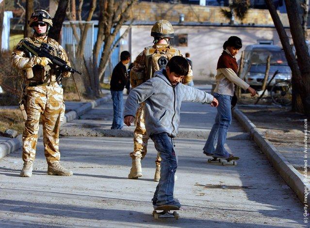 Afghan kids skateboard near their homes along side British ISAF soldiers on patrol