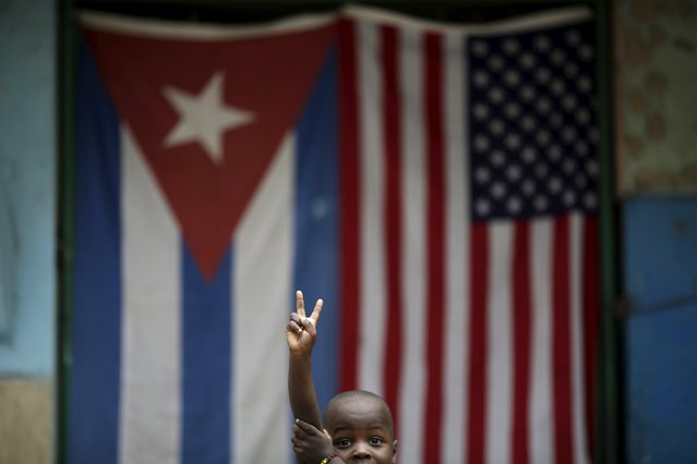 Eric, 3, gestures while posing for a photograph in front of the Cuban and U.S. flags in Havana, March 25, 2016. (Photo by Ueslei Marcelino/Reuters)