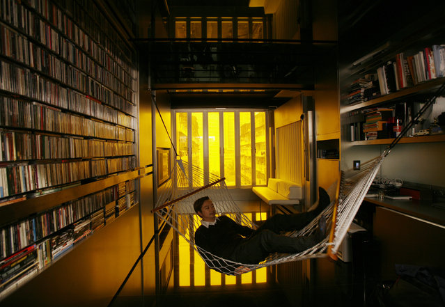 "Hong Kong architect Gary Chang rests in a hammock inside his 32-square-metre apartment in Hong Kong January 28, 2010. After three decades in the same boxy dwelling Chang grew up in, he came up with an innovative answer to the increasingly cramped lives of many urban dwellers – the science fiction-like ""domestic transformer"". (Photo by Bobby Yip/Reuters)"