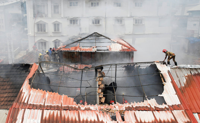 A firefighter walks on the rooftop as others try to douse a fire that broke out at a wholesale market in Kochi, India, May 27, 2019. (Photo by Sivaram V/Reuters)