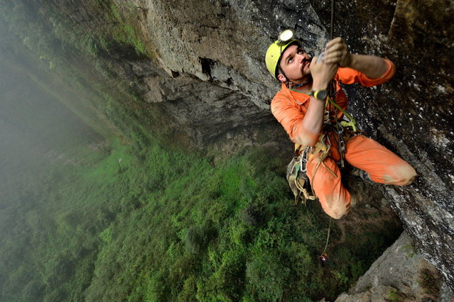 Gaining height step by step Hong Meigui member; Duncan Collis climbs a thin rope up to a small ledge overlooking the vast floor surface of Niubizi Tian Keng in the Er Wang Dong cave system. (Photo by Robbie Shone/Caters News/ImagineChina)