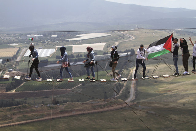 A Palestinian living in Lebanon with a small Palestinian flag leads other women as men hold up a bigger one on a suspension bridge, overlooking Israeli settlements during a protest marking the 67th anniversary of Nakba, or Catastrophe, at Iran park in the southern Lebanese-Israeli border village of Maroun el-Rass, Lebanon, Thursday, May 14, 2015. Protesters commemorated on Thursday the dispersal of Palestinians over Israel's creation during the first Israeli-Arab war in 1948. (Photo by Mohammed Zaatari/AP Photo)