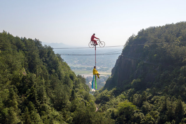 Men perform high-wire stunts on a tightrope in the Shiniuzhai national geological park in Yueyang, Hunan province, China on June 4, 2019. (Photo by Reuters/China Stringer Network)