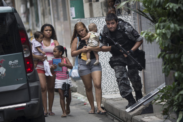 "Upon hearing gun shots, a military police officer runs for cover, past residents, during an operation in the Mare slum complex, ahead of its ""pacification"", in Rio de Janeiro, Brazil, Tuesday, March 25, 2014. Elite federal police and army troops will be sent to the city to help quell a wave of violence in so-called ""pacified"" slums. (Photo by Felipe Dana/AP Photo)"