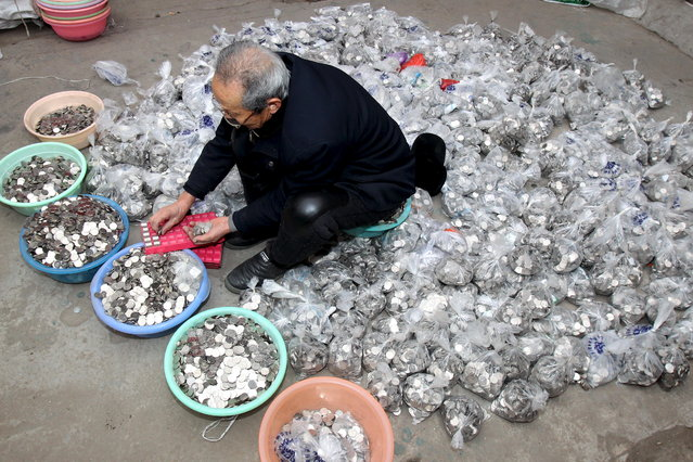 A man counts coins collected from coin-operated laundry machines, at a warehouse in Zhengzhou, Henan province, China, January 11, 2016. A man running a coin-operated laundromat service had failed to exchange 300,000 yuan ($45,609) worth of coins into banknotes to pay his employees 3 months worth of salaries, according to local media. Local banks said they are unable to process the exchange in a go, the reports added. (Photo by Reuters/China Stringer Network)