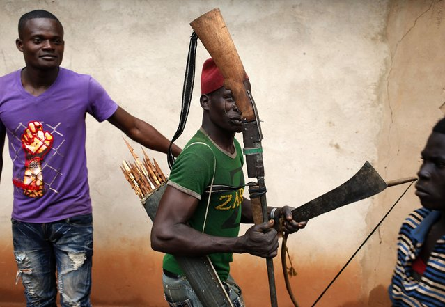 A member of the anti-balaka, a Christian militia, walks with his weapons in the village of Zawa April 8, 2014. (Photo by Goran Tomasevic/Reuters)