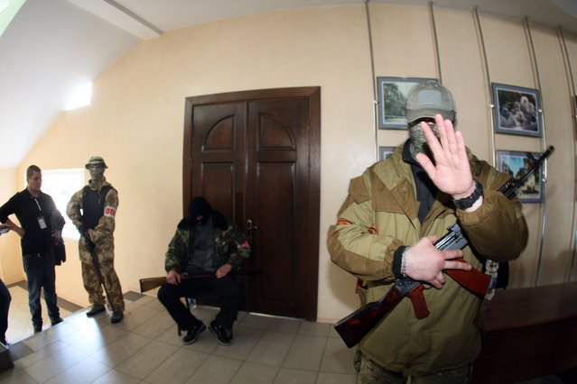 Armed pro-Russia activists stand guard inside the city state building they seized in the eastern Ukrainian city of Donetsk, on April 16, 2014. (Photo by Reuters/Stringer)