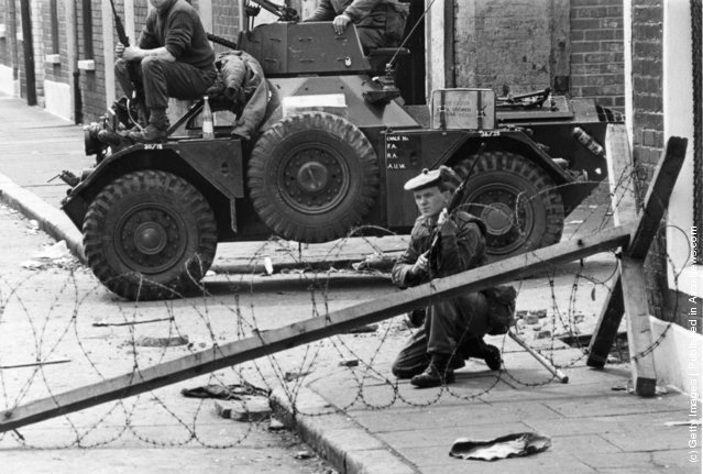 1970:  British troops and a Ferret armoured car guard a sectarian divide on the streets of Belfast