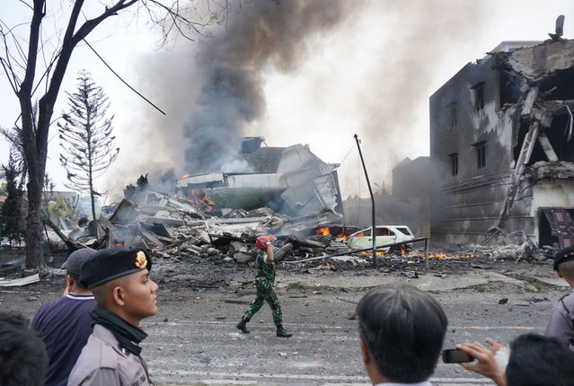 Indonesian police and military officials secure the crash site of military Hercules plane in Medan, North Sumatra province on June 30, 2015. (Photo by Muhammad Zulfan Dalimunthe/AFP Photo)