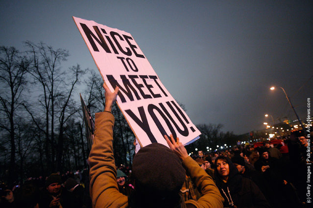 Protesters hold flags and banners aloft as they march in Bolotnaya Square on December 10, 2011 in Moscow, Russia