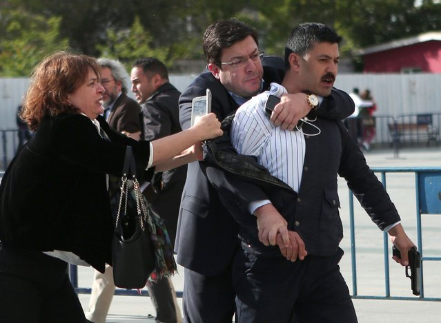 This picture released by Turkish Cumhuriyet Daily newspaper shows Dilek Dundar (L), the wife of editor-in-chief of Turkish newspaper Cumhuriyet daily Can Dundar, trying to stop a gunman who is also being held back by a man on May 6, 2016 in Istanbul. Turkish opposition journalist Can Dundar escaped a shooting on May 5 outside a courthouse in Istanbul where he is on trial, adding police detained the assailant. (Photo by AFP Photo/Cumhuriyet Daily Newspaper)