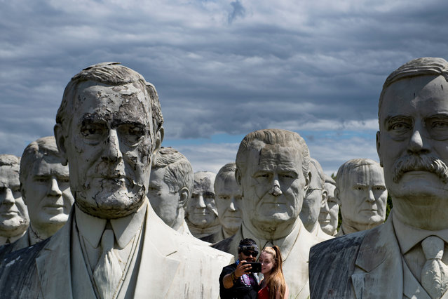 A couple poses for a selfie with giant salvaged busts of former US Presidents August 25, 2019, in Williamsburg, Virginia. Howard Hankins rescued the giant busts of former US Presidents from the closed Presidents Park in Colonial Williamsburg when he was commissioned to destroy them. (Photo by Brendan Smialowski/AFP Photo)