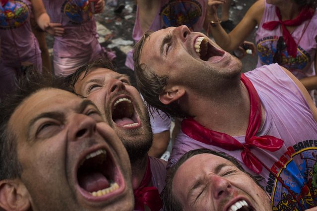 Revelers open their mouths as they wait to cool off with water thrown from a balcony to celebrate the official opening of the 2015 San Fermin Fiestas, in Pamplona, northern Spain, Monday, July 6, 2015. (Photo by Andres Kudacki/AP Photo)