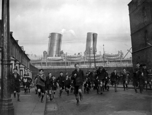 Children pour out of their School in Drew Street, Silvertown, in the east end of London, with the liner Rajputana in the background, 15th January 1932. (Photo by Popperfoto/Getty Images)