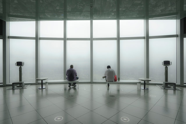 """Observatory"". On a heavy rainy day, at the observatory of Roppongi Hills of Tokyo, Japan. The panoramic view was veiled in a haze. The useless observatory seemed to be a secret place for serene contemplation. Photo location:  Roppongi Hills, Tokyo, Japan. (Photo and caption by Takeo Hirose/National Geographic Photo Contest)"