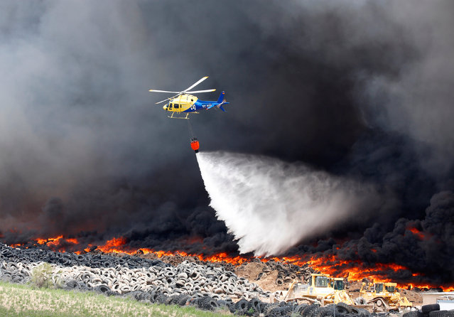 An helicopter throws water over a fire at a tire dump near a residential development in Sesena, south of Madrid, Spain, May 13, 2016. (Photo by Sergio Perez/Reuters)