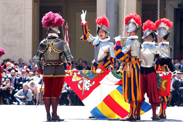A new recruit raises three fingers in the sign of the trinity at a swearing in ceremony for the Vatican's elite Swiss Guard at the Cortile di San Damaso at The Vatican on May 6, 2014 in Vatican City, Vatican. The swearing in ceremony is held on May 6 every year to commemorate the 147 halberdiers who died defending the pope in 1527. (Photo by Franco Origlia/Getty Images)
