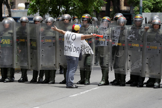 """An opposition supporter carrying a banner that reads """"There is not food"""" shouts to Venezuelan National Guards during clashes in a rally to demand a referendum to remove President Nicolas Maduro in Caracas, Venezuela, May 18, 2016. (Photo by Marco Bello/Reuters)"""