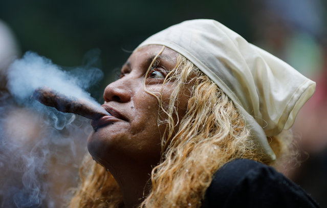 "In this photo taken October 12, 2019, a spiritual healer known as a ""madrina"" starts a ritual on Sorte Mountain where followers of indigenous goddess Maria Lionza gather annually in Venezuela's Yaracuy state. While her followers gather on the mountain for weeks at this time of the year, October 12 marks the biggest gathering, coinciding with Indigenous People's Day, known in Latin America as ""Dia de la Raza"". (Photo by Ariana Cubillos/AP Photo)"