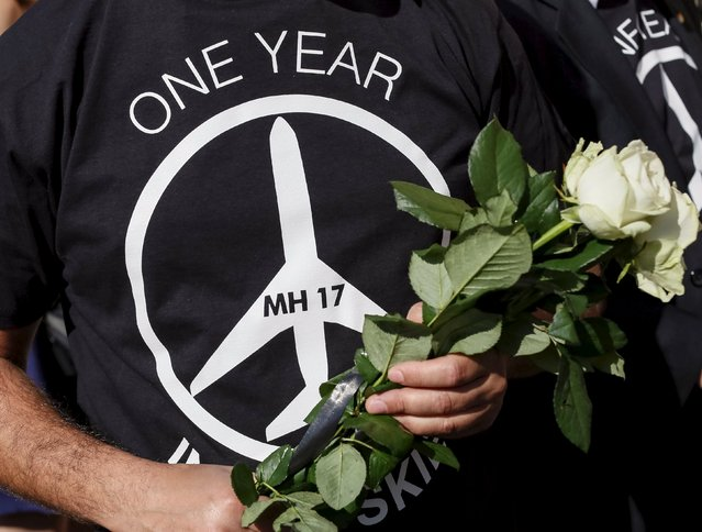 A man carries flowers outside the Dutch embassy to commemorate the victims of the downing of Malaysia Airlines MH17 in eastern Ukraine a year ago, in Kiev, Ukraine July 17, 2015. British Foreign Secretary Philip Hammond on Friday backed calls for an international tribunal to prosecute those suspected of shooting a Malaysian airline out of the sky over rebel-held eastern Ukraine a year ago. (Photo by Gleb Garanich/Reuters)