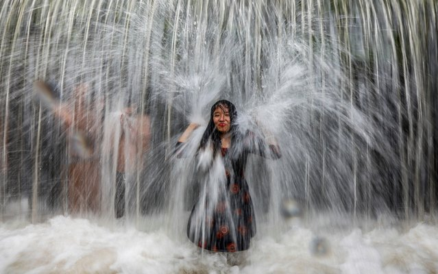 A Nepalese woman stands under a waterfall as people gather to enjoy the weekend at Muhanpokhari, Bhaktapur, Nepal, 31 August 2019. (Photo by Narendra Shrestha/EPA/EFE/Rex Features/Shutterstock)