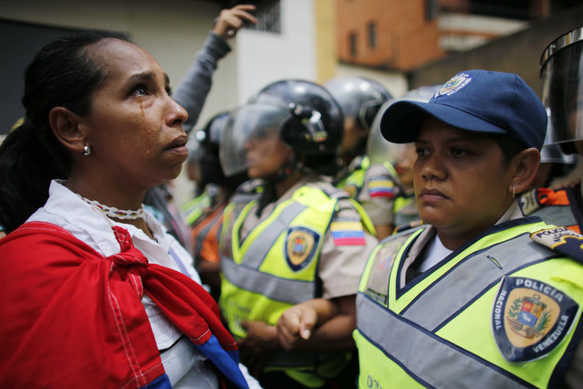 A demonstrator stands in front of policewomen blocking an opposition march from reaching the Interior Ministry in Caracas, Venezuela, Saturday, May 6, 2017. Thousands of women wearing white and carrying flowers marched to ask for a stop of repression and to pay tribute to those who were killed in weeks of near-daily violent protests calling on President Nicolas Maduro to step down. (Photo by Ariana Cubillos/AP Photo)