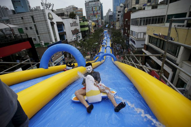 A man wearing a Guy Fawkes mask enjoys a ride on a 350-meter (1148 feet) long water slide during 2015 City Silde Festa in central Seoul, South Korea, July 19, 2015. (Photo by Kim Hong-Ji/Reuters)