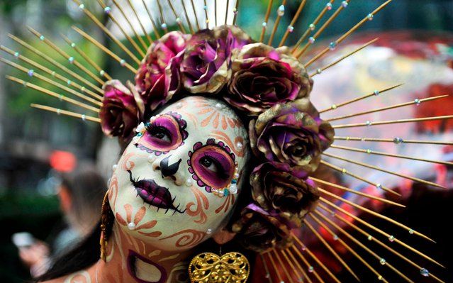 """A woman fancy dressed as Catrina takes part in the """"Catrinas Parade"""" along Reforma Avenue, in Mexico City on October 26, 2019. Mexicans get ready to celebrate the Day of the Dead highlighting the character of La Catrina which was created by cartoonist Jose Guadalupe Posada, famous for his drawings of typical local, folkloric scenes, socio-political criticism and for his illustrations of """"skeletons"""" or skulls, including La Catrina. (Photo by Claudio Cruz/AFP Photo)"""