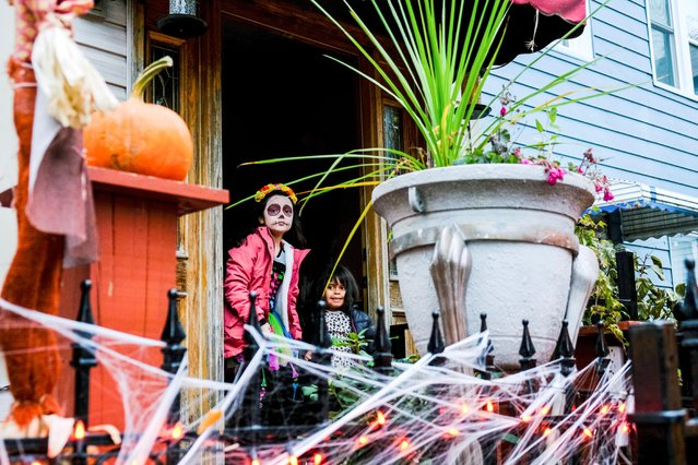 A girl and boy peek outside their home as Mexican-American community of Pilsen celebrate Day of the Dead with a procession through their neighborhood in Chicago, Illinois, November 2, 2019. (Photo by Maria Alejandra Cardona/Reuters)