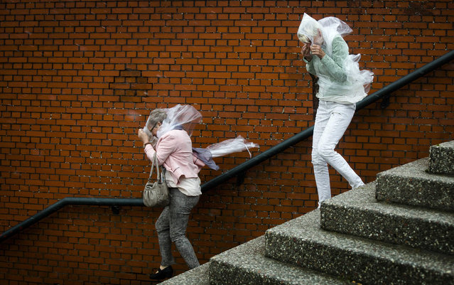 Pedestrians struggle with the wind near the coast in Scheveningen, The Netherlands, 25 July 2015. A heavy storm is forecast in the area. (Photo by Bart Maat/EPA)