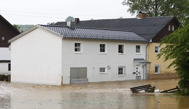 A woman looks out from a window of a house in the flooded Bavarian village of Triftern east of Munich, Germany, june 1, 2016. (Photo by Michaela Rehle/Reuters)