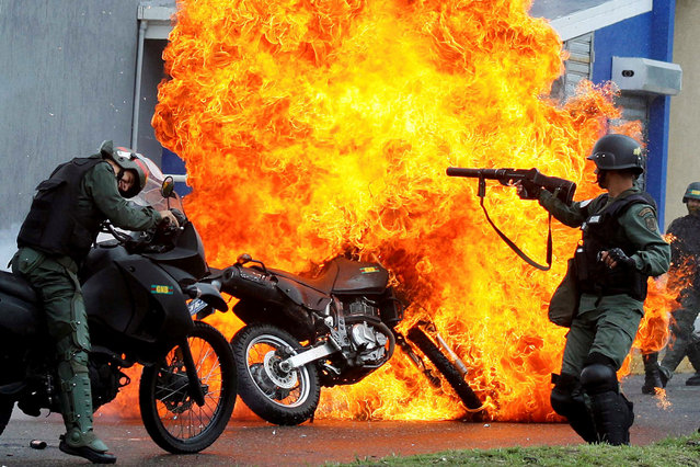 Riot security forces clash with demonstrators as a motorcycle is set on fire during a protest against Venezuelan President Nicolas Maduro's government in San Cristobal, Venezuela May 29, 2017. (Photo by Carlos Eduardo Ramirez/Reuters)