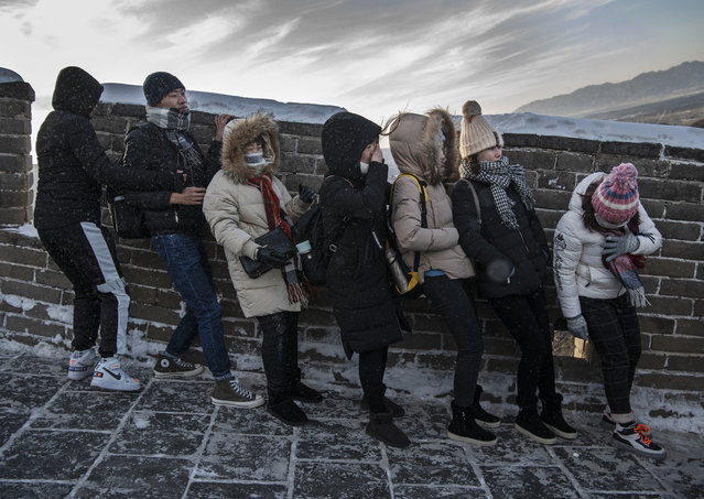 Chinese tourists struggle to walk down in heavy wind on an icy section of the Great Wall at Badaling, on a cold day after a snowfall on November 30, 2019 in Beijing, China. (Photo by Kevin Frayer/Getty Images)