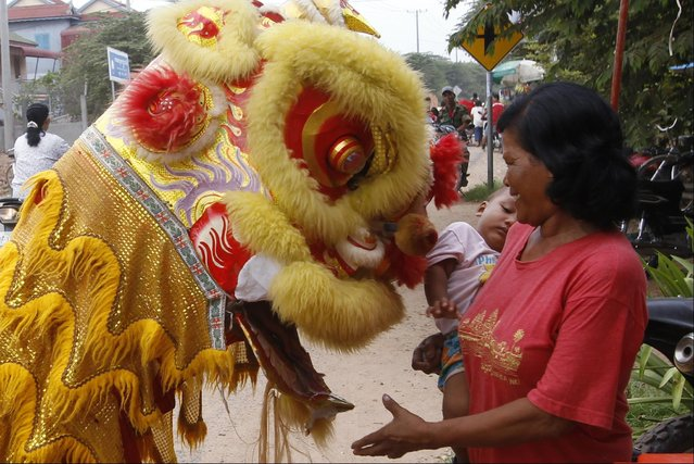 "A Cambodian villager, right,  holds her grandchild as she offers some money during a performance of a local lion dance called ""Mong Say"" during Buddhist Lent in Prek Takov village, Kandal province, northeast of Phnom Penh, Cambodia, Monday, July 27, 2015. (Photo by Heng Sinith/AP Photo)"