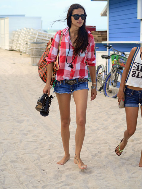Brazilian supermodel Adriana Lima was pictured smiling and happy as she enjoyed a beautiful afternoon on the beach in Miami Beach with a female friend, on June 15, 2014. It was one month after announcing her seperation from husband of five years, former NBA player Marco Jaric. (Photo by Fred Montana/Splash News)