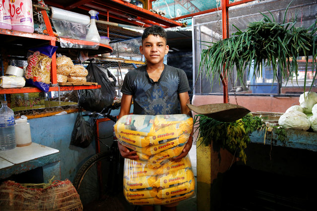 Carlos Cure holds packets of corn flour made in Colombia as he poses for a picture at a stall that sells food and staple items at a market in La Fria, Venezuela, June 2, 2016. (Photo by Carlos Garcia Rawlins/Reuters)