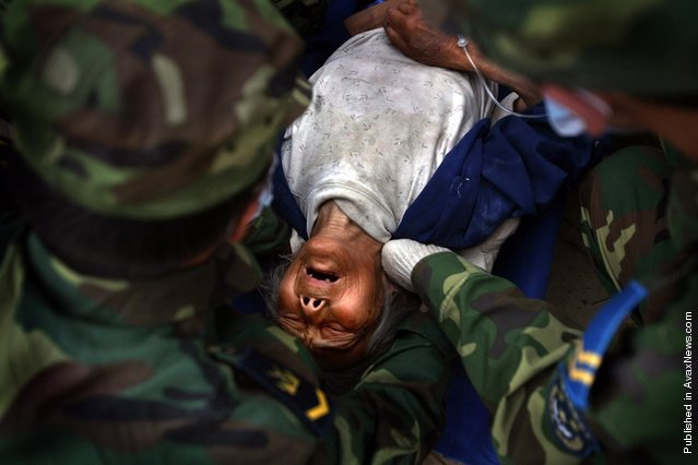 A Chinese earthquake survivor is lifted by Chinese soldiers in the town of Mianzhu in China's southwest Sichuan province to be taken by ambulance to another city for treatment May 24, 2008