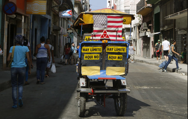 """A taxi tricycle displays a representation of a U.S. national flag, as well as a Cuban national flag, with signs that read in Spanish; """"there is no limit here"""", in Havana, Cuba, Saturday, April 11, 2015. (Photo by Desmond Boylan/AP Photo)"""