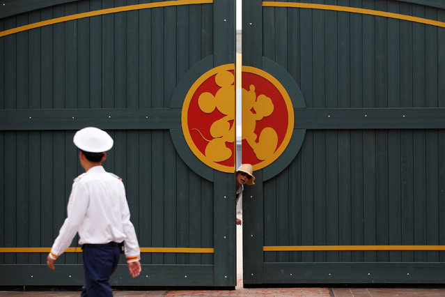 A woman stands outside a gate in Shanghai Disney Resort during a three-day Grand Opening events in Shanghai, China, June 15, 2016. (Photo by Aly Song/Reuters)